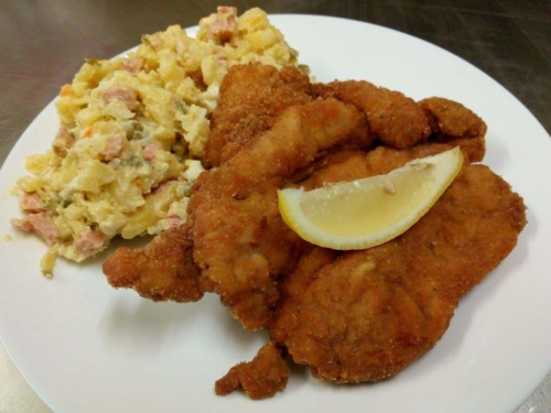 Schnitzel and potato salad (with carrot, peas, ham, eggs and onion), traditionally meal on Christmas